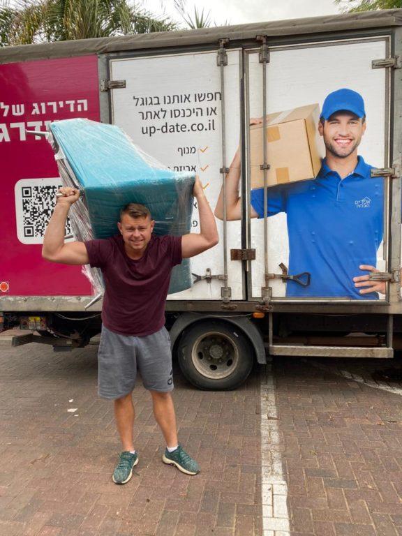 איש צוות אפדייט הובלות מרים ציוד ליד משאית במהלך הובלות ברחובות