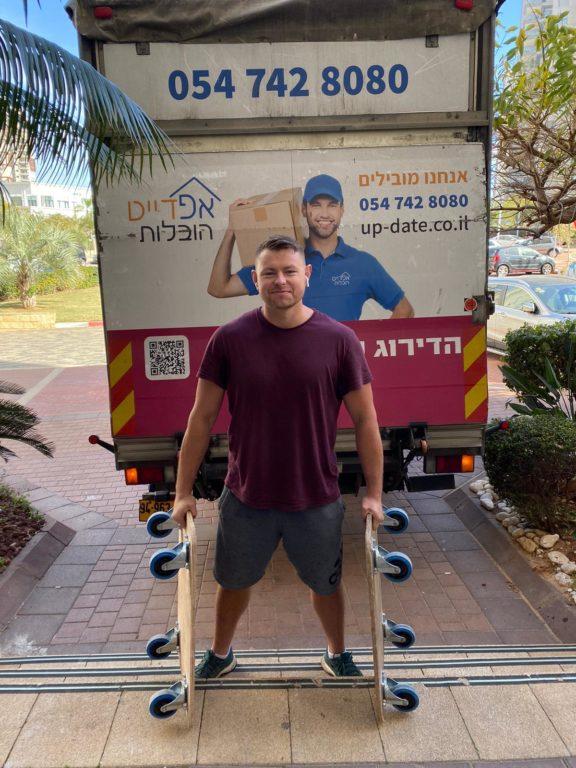 איש צוות של אפדייט הובלות ליד משאית במהלך הובלות דירה בחולון