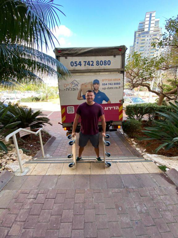 איש צוות של אפדייט הובלות מצטלם ליד משאית ההובלה במהלך הובלות דירה בתל אביב