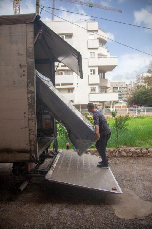 מעבירים ציוד ממשאית ההובלה במהלך הובלות דירה בתל אביב