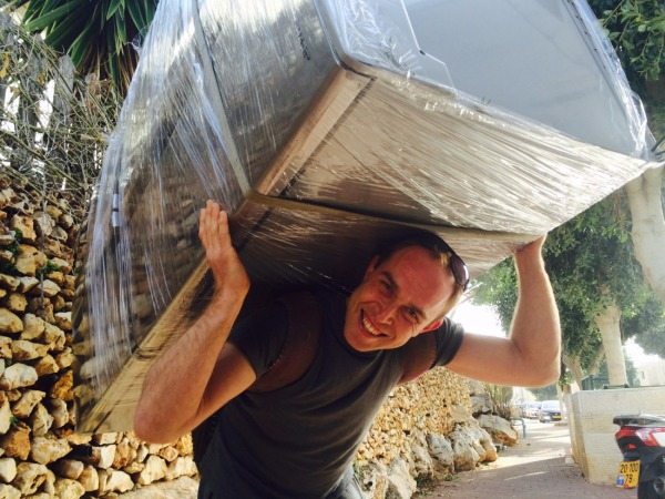 סלאבה, הבעלים של אפדייט הובלות מחייך למצלמה במהלך הובלה ברעננה
