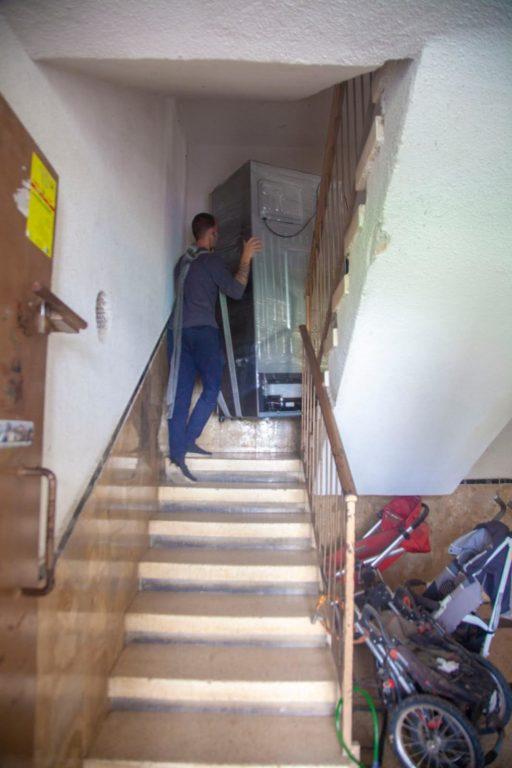 מעלים ציוד במדרגות הבניין במהלך הובלות בנתניה